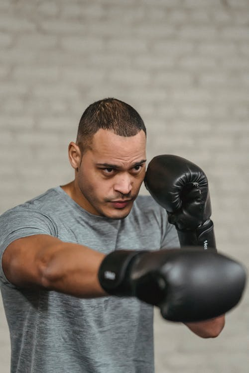 Ethnic boxer demonstrating punching technique during training on gray background