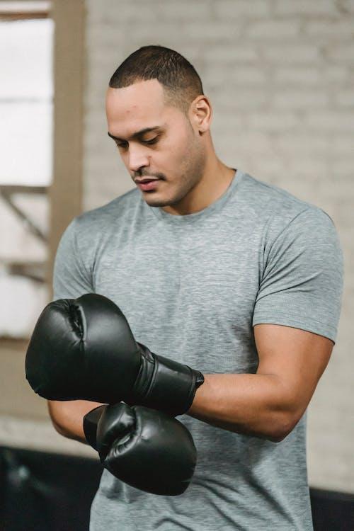 Hombre En Camiseta Gris De Cuello Redondo Con Guantes De Boxeo Negros
