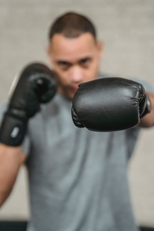 Strong ethnic fighter showing punching technique during training