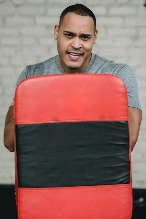 Hombre En Camiseta Gris Con Cuello Redondo Sosteniendo Silla Roja Y Negra