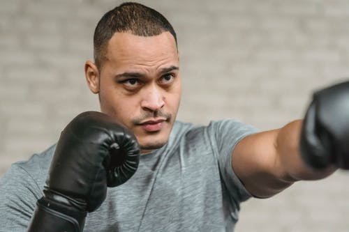 Strong ethnic sportsman in boxing gloves performing punching technique while looking forward during training on blurred gray background