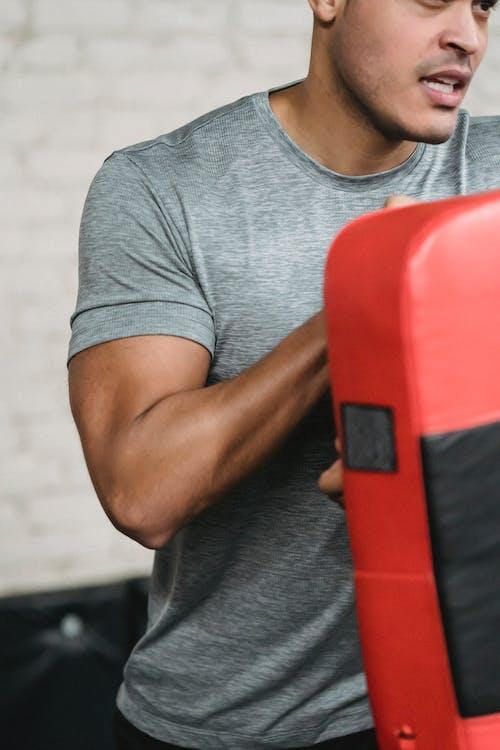 Serious muscular ethnic guy boxing in studio