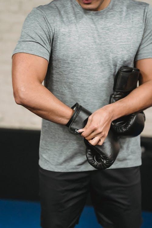 灰色のtシャツと黒革のボクシンググローブの男
