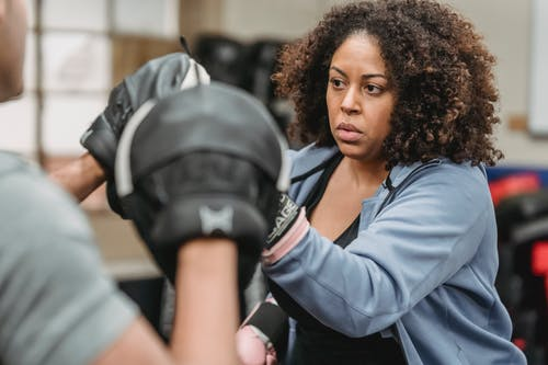 Serious black lady boxing in gym during training with male instructor