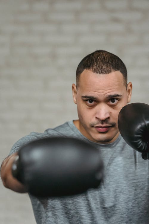 Confident young strong ethnic male boxer in activewear and gloves punching and looking at camera during workout in boxing club