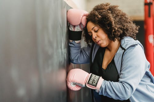 Side view of tired young African American female fighter with dark curly hair in sportswear and protective gloves leaning on wall after boxing workout in gym