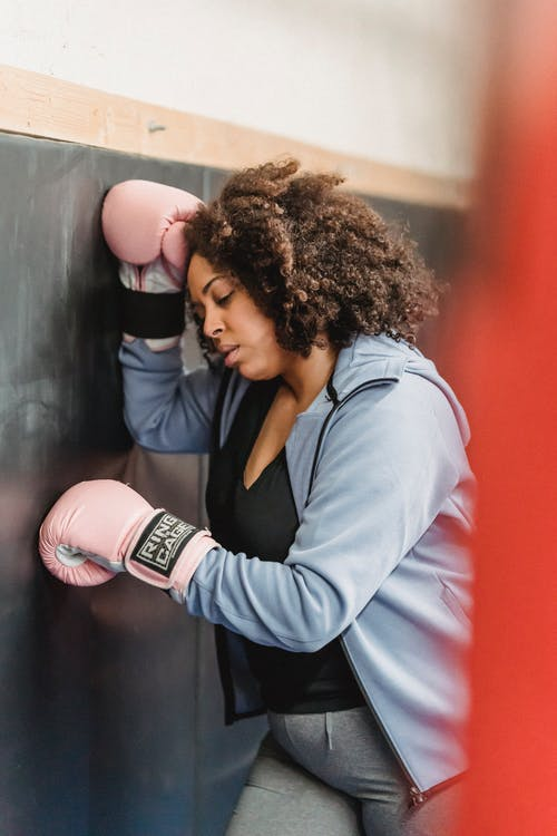 Tired young ethnic lady resting near wall after boxing workout