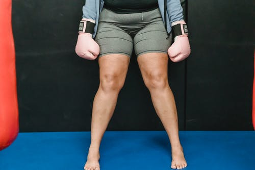 Crop anonymous barefooted overweight lady in activewear and boxing gloves standing in ring before workout