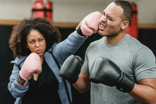 Determined young African American female fighter in activewear and boxing gloves punching in face of ethnic male coach during training in ring