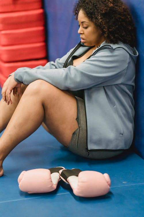 Young overweight black lady resting in gym after boxing workout
