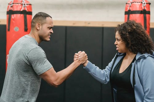 Side view of angry African American couple clasping hands and looking at each other while showing strength during workout in boxing gym
