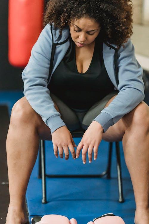 Siyah Kolsuz Bluz Ve Gri Hırka Mavi Sandalyede Oturan Kadın