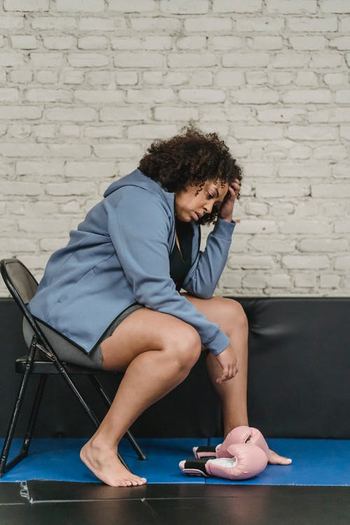 Full body side view of exhausted plump African American female sitting on chair near boxing gloves on mat during workout