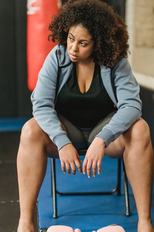 Black overweight woman sitting in gym