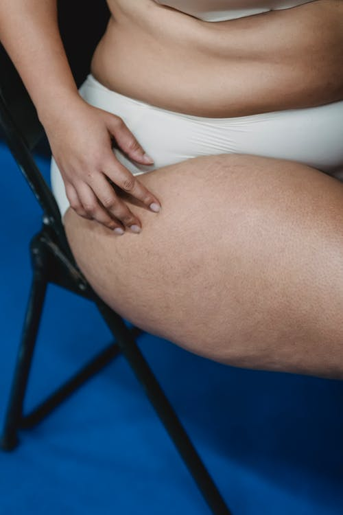 青い椅子に座っている白いビキニの下の女性