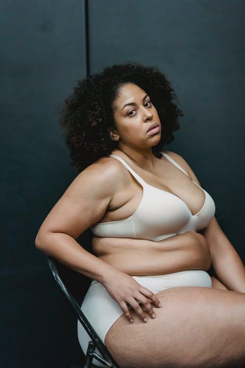 Donna In Bikini Bianco Che Si Siede Sulla Sedia