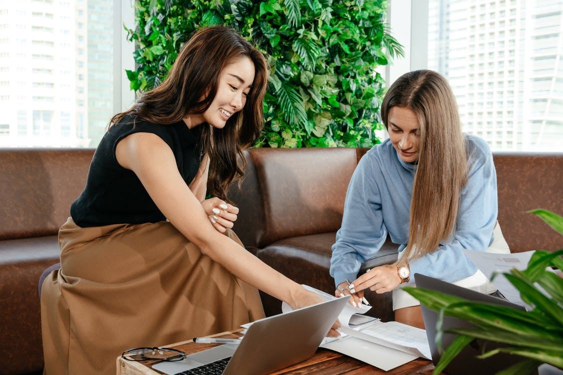 Cheerful diverse women working with documents at table with laptop