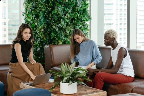 Diverse focused women working with papers and laptop