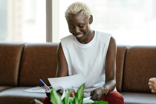 Smiling black woman checking contract on leather sofa