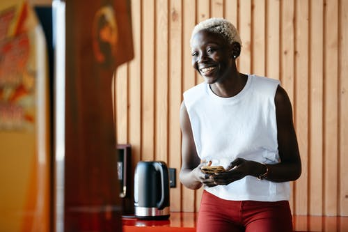 Young happy black woman using smartphone in office kitchen