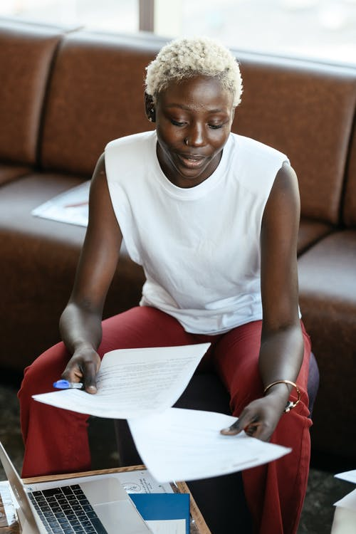 Experienced black businesswoman working with papers at table with laptop