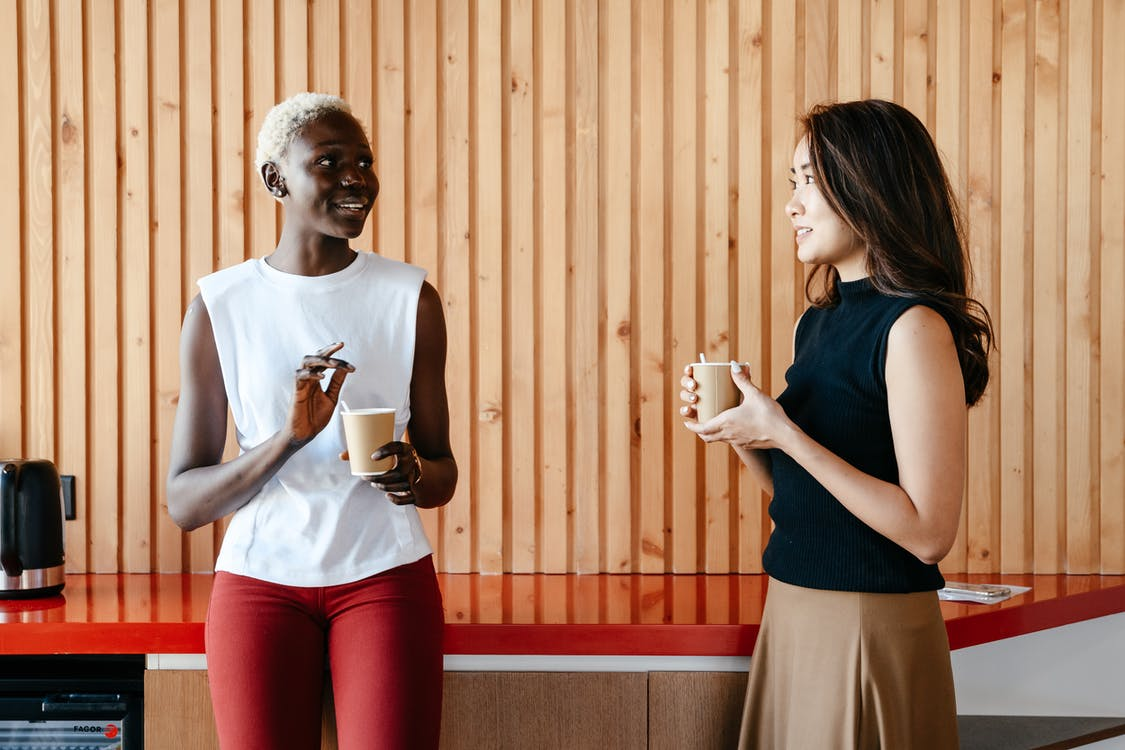 Happy multiracial women with cups of coffee smiling and discussing job in contemporary office