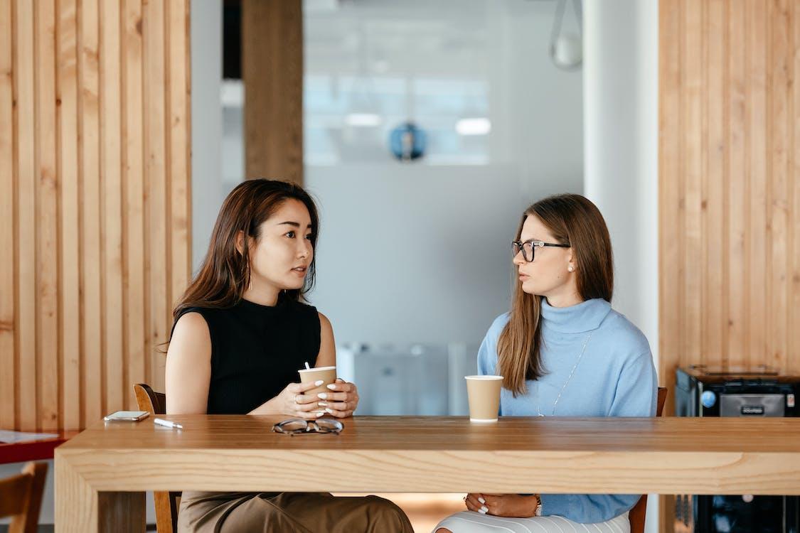 Diverse women talking during coffee break at table