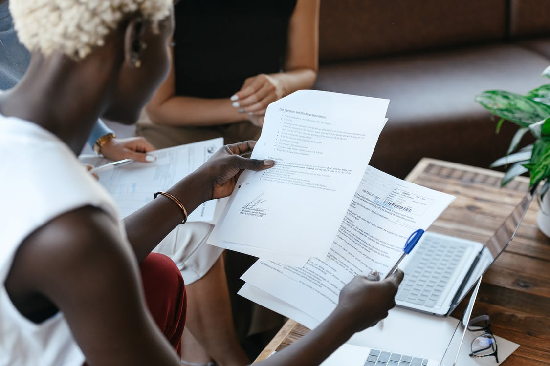 From above of crop anonymous African American female comparing data in papers at table of office