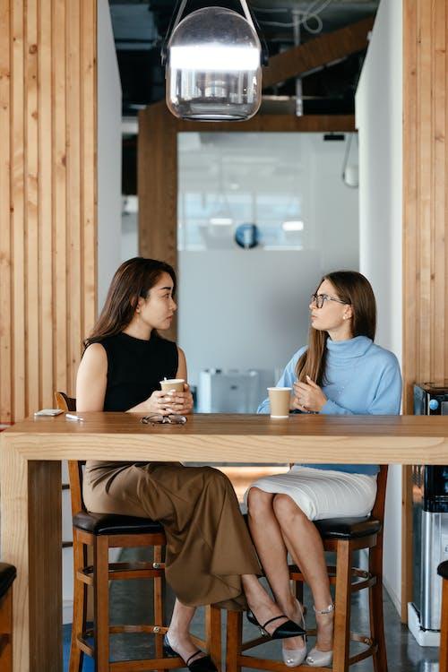 Serious multiethnic businesswomen discussing job during coffee break