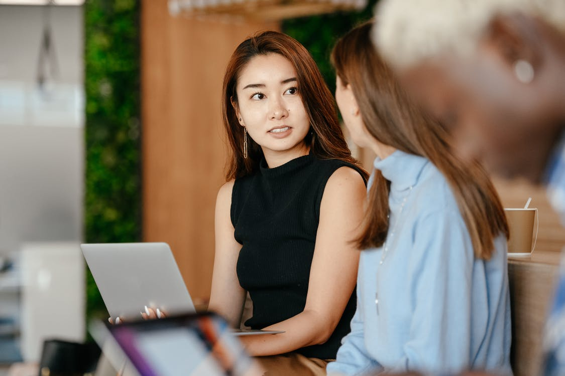 Asian woman discussing business plan with diverse colleagues