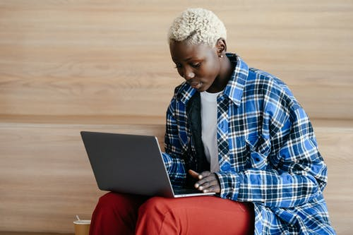 Young serious African American female in trendy blue checkered shirt using netbook and freelancing