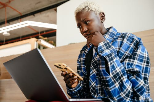 Young serious African American female in blue checkered shirt looking at screen of netbook while texting message on mobile phone
