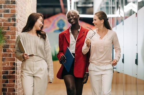 Group of young glad businesswomen in trendy elegant outfits smiling and discussing business strategy in contemporary workspace