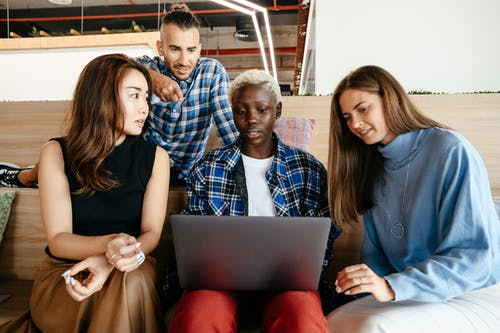 Multiethnic coworkers watching plan on laptop