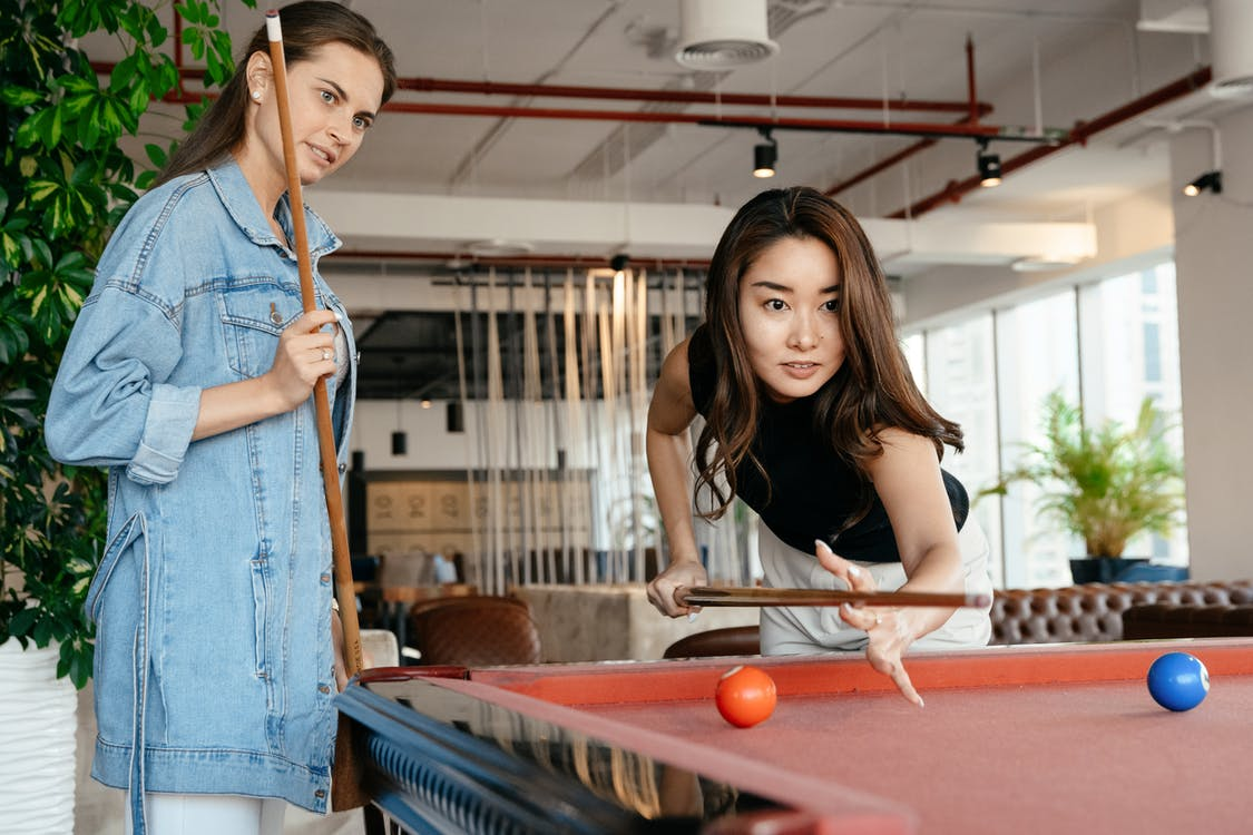 Diverse friends playing billiard at home