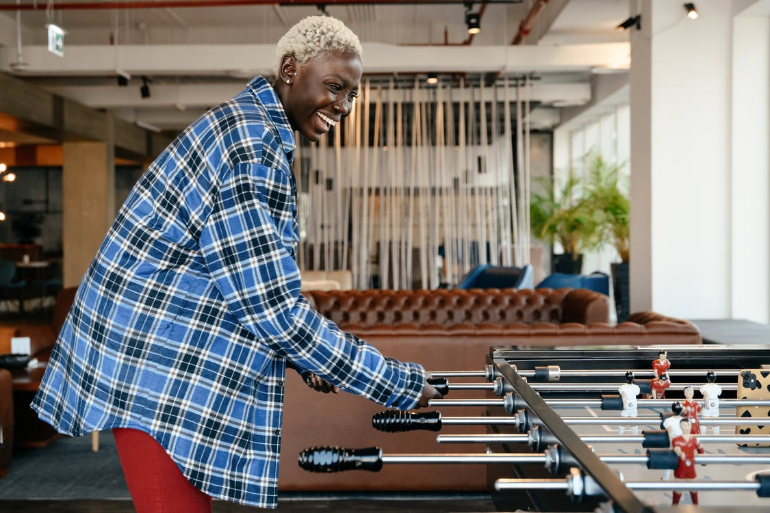 Side view of smiling African American female in casual clothes standing and playing foosball in living room at home