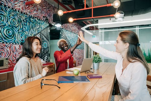 Group of positive young multiethnic female colleagues smiling and giving high five while sitting at wooden table with documents and laptop in creative workspace