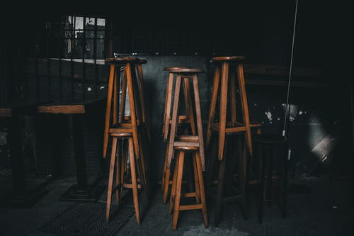 Timber bar stools and tables in aged shabby building of cafe with window with metal lattice