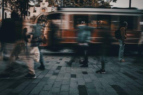 Anonymous people walking on city street near public transport