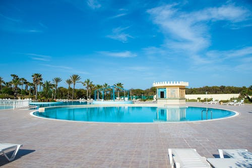 Round swimming pool located in terrace of hotel with deckchairs ad exotic palms in tropical country in sunny summer day