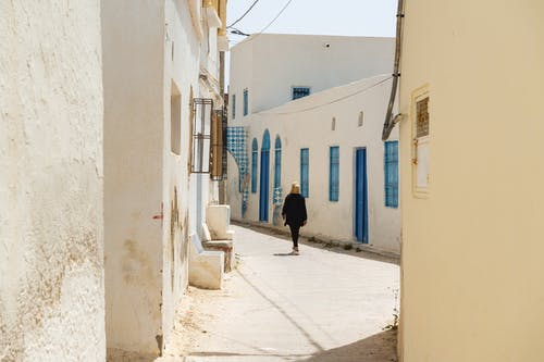 Unrecognizable person walking on narrow street in old town