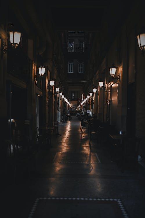 Dark narrow street amidst old residential buildings and vintage lanterns