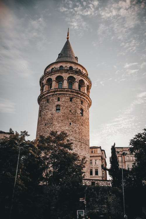 From below of aged famous Galata Tower with arched windows and sharp roof located in Istanbul against cloudy sky