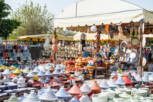 Stalls of assorted traditional dishes and plates with bright colors on local bazaar on sunny street with green trees in city