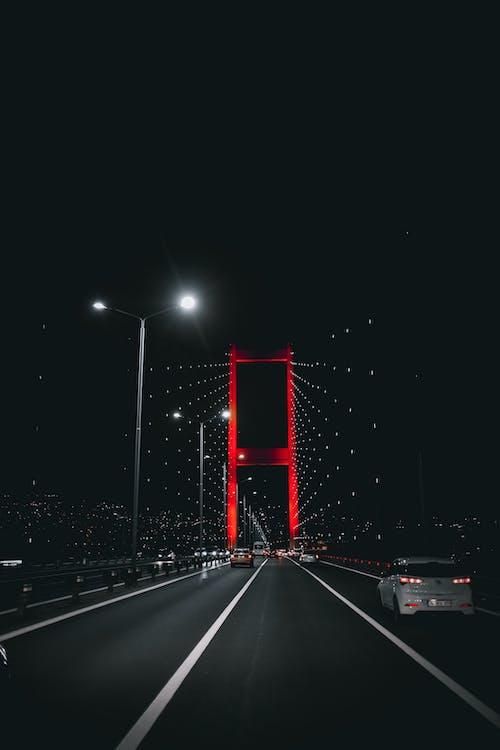 Vehicles driving on illuminated bridge under night sky