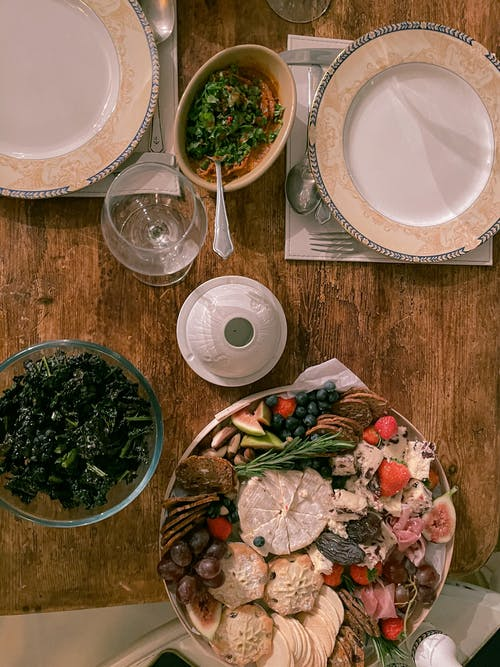 Vegetable Salad on White Ceramic Plate Beside Clear Drinking Glass on Brown Wooden Table