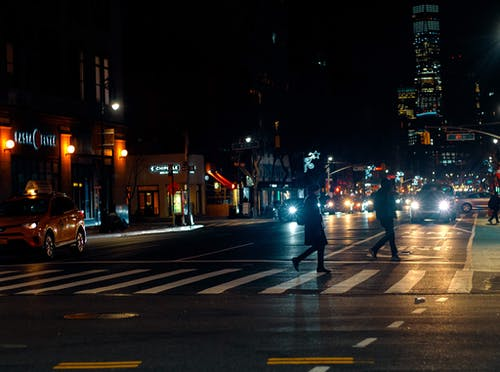 Pedestrian crossing busy road in modern city in autumn evening