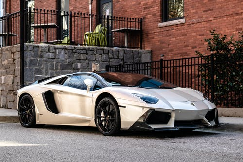 White and Blue Lamborghini Aventador Parked Beside Brown Brick Wall