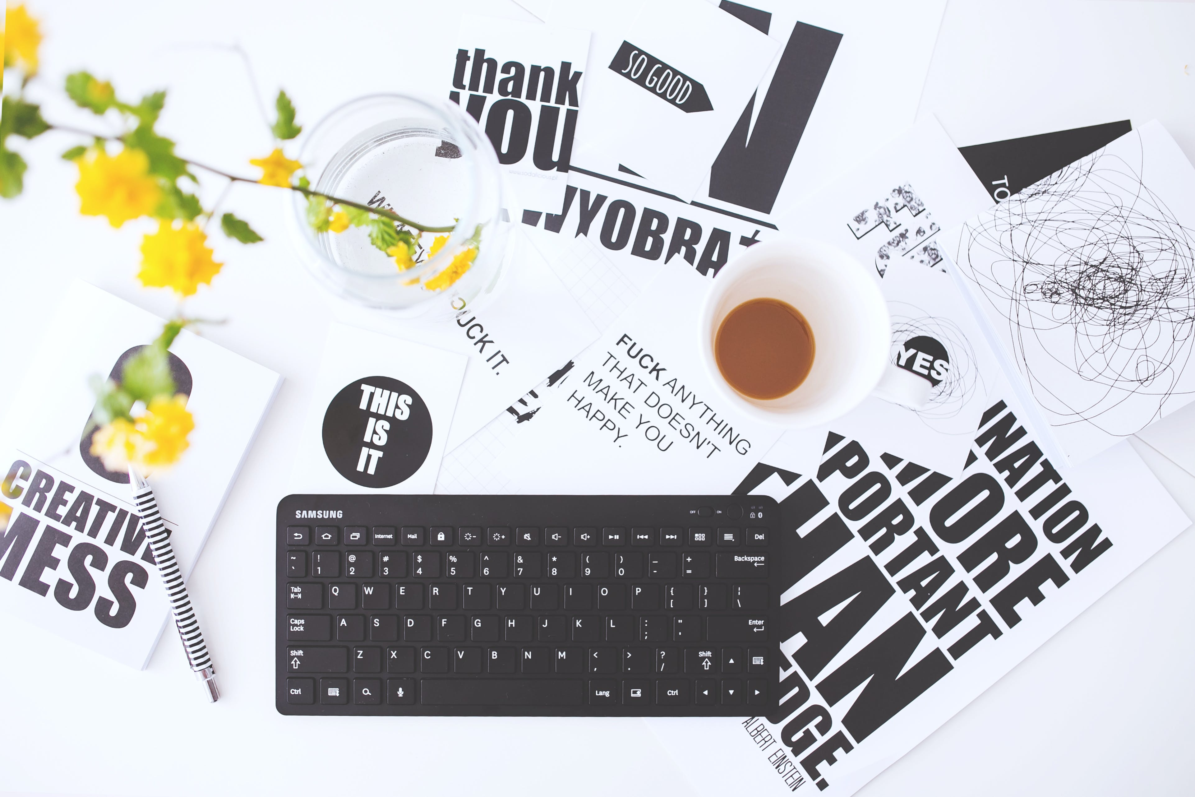 Top view of creative workspace with keyboard and coffee