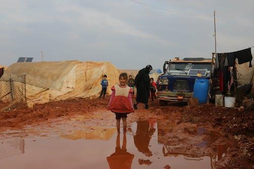 Joyful ethnic girl standing in dirty puddle